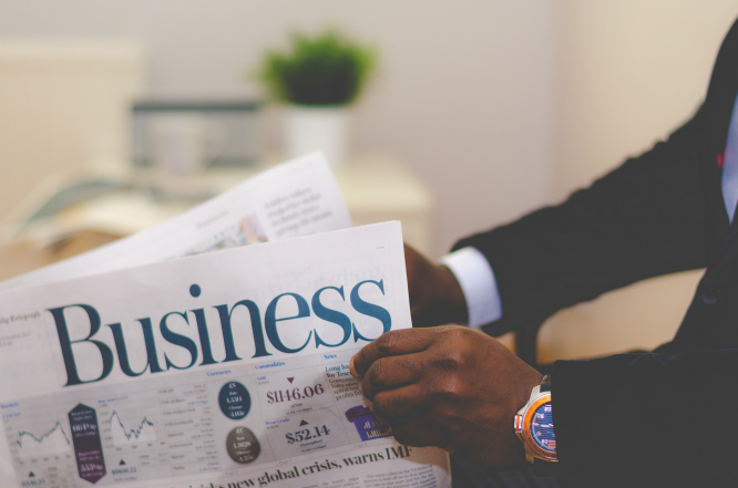 Person wearing a suit reads a business paper. Article: Robert Kent on why it's wise to read between the financial media lines. Photo by Adeolu Eletu / Unsplash