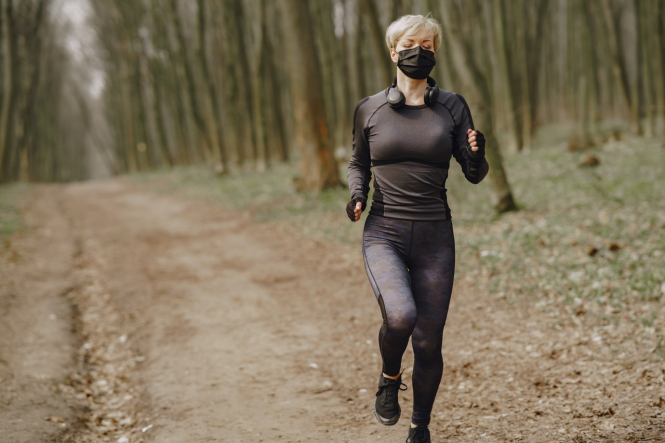 A woman running while wearing a mask. Joggers and cyclists in Paris must use mask in crowded areas
