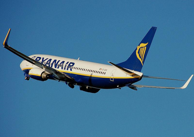 Ryanair jet in three-quarter view from the rear against blue sky