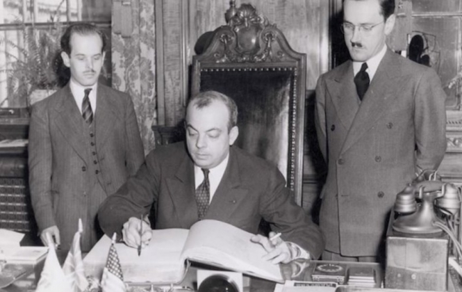 Saint-Exupéry signs a book at a desk with an American flag visible. Saint-Exupéry Petit Prince author and 'mystery American' letters sold in Paris book shop