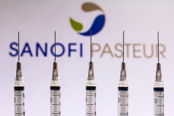 Medical syringes seen with Sanofi Pasteur company logo in background. French-made Sanofi Covid vaccine moves a step closer to use in EU