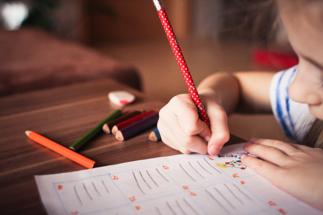 A young girl writing and colouring. Covid France: Schools to do one million tests per month