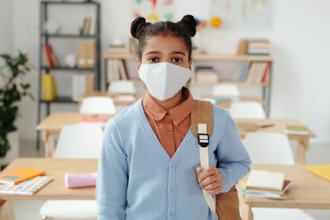 A child wears a mask in a classroom. France sets stricter Covid protocol for schools including masks and distancing