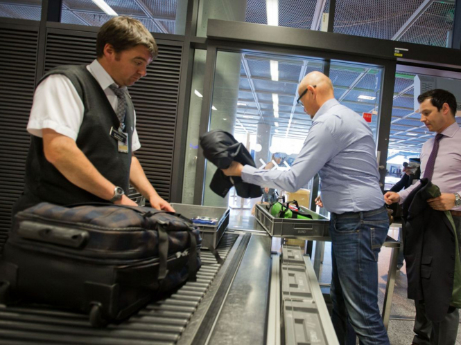 Men in line for baggage security check at airport