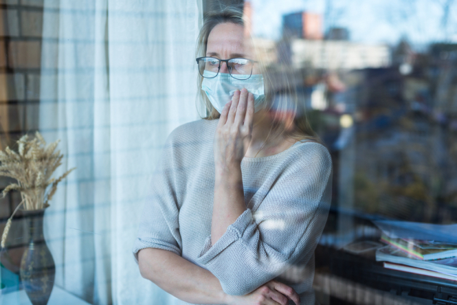 Woman stands and looks out the window wearing a mask, during self-isolation. Covid rules: When are you required to self-isolate in France?