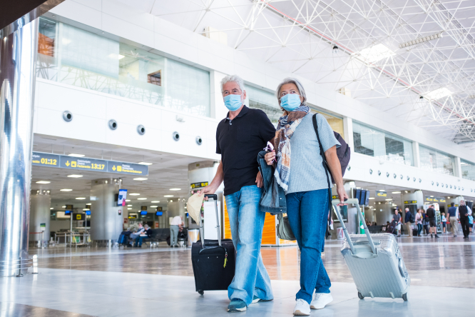 Two people with facemasks at an airport