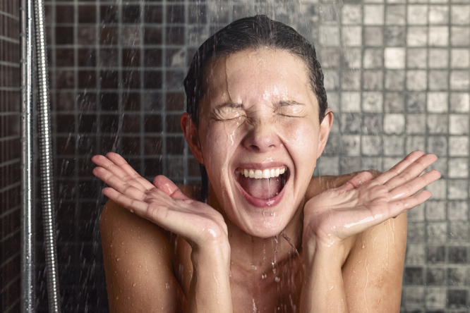 Young woman reacting in shock to cold shower water. Hot weather continues in France: 10 things not to do in a heatwave