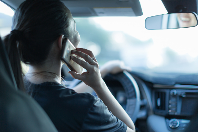 An image of a woman talking on the phone while driving