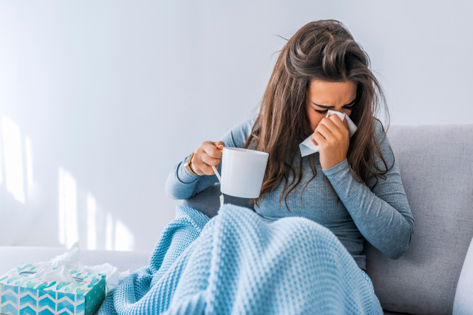 An image of a woman sitting under a blanket sneezing into a tissue