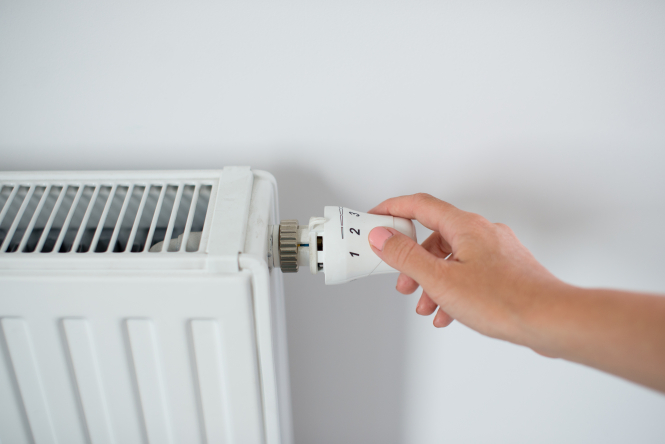 An image of a woman's hand adjusting the temperature on a radiator