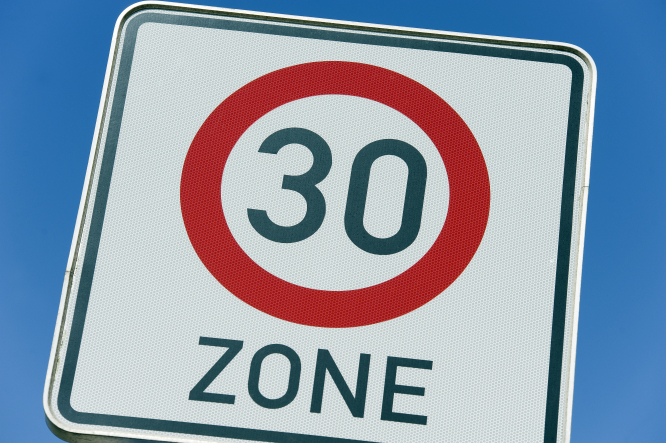 A road sign reading 30kph and the word ZONE, with blue sky behind.