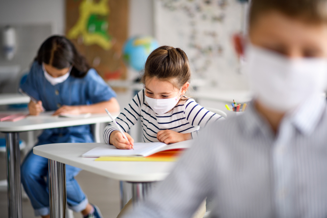 An image of three young children in a classroom sitting at desks with their masks on