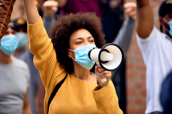 A woman wearing a mask and holding a megaphone raises her fist in the air during a protest with other people wearing masks behind her