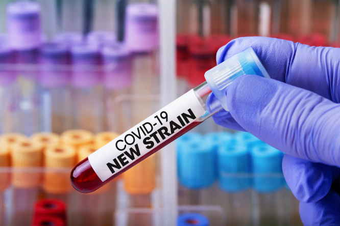 """A laboratory technician holding a test tube with blood, labelled """"Covid-19 New Strain"""""""