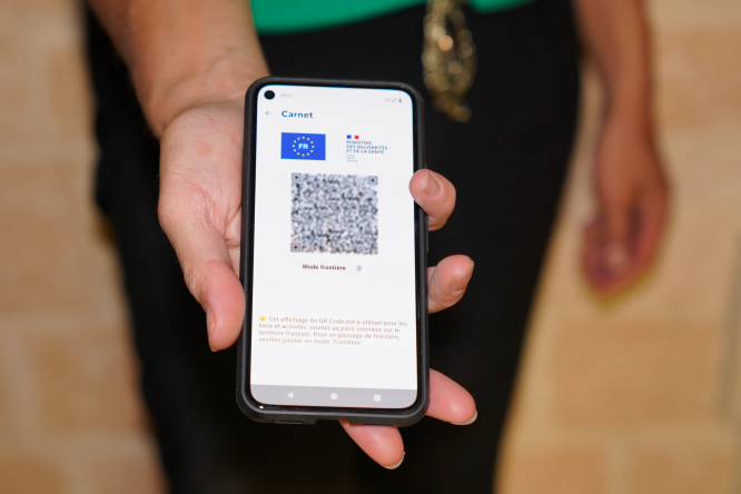 A health pass code on a smartphone screen in hand, in Bordeaux, France