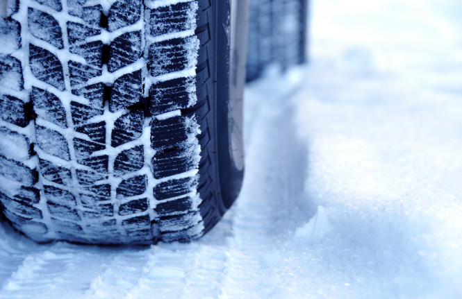 An image of a winter tyre driving through snow