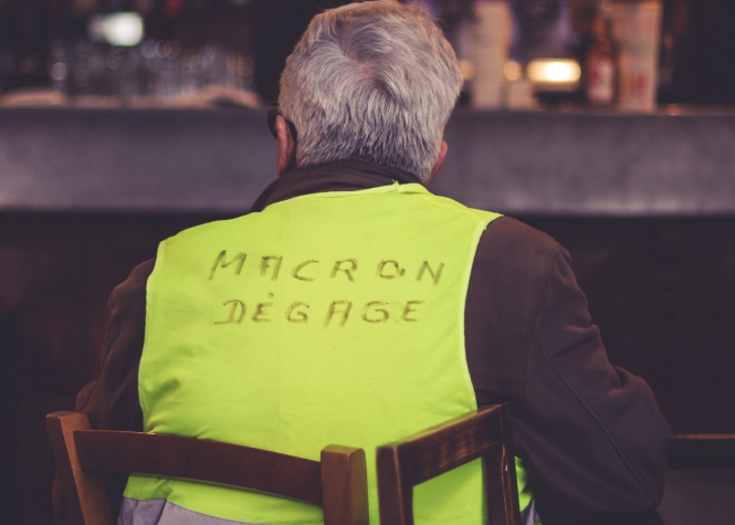 A person in Lyon, France wears a yellow vest which reads 'Macron degage'. Article: Simon Heffer on what has led President Macron to this point of threats of derailment. Photo by ev / Unsplash