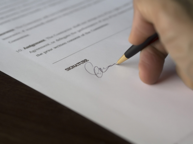 A man signs a form. France requires new travel forms, with separate form for UK