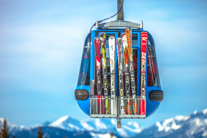 Skis on a cable car against a bright blue sky. Thousands of ski jobs are in jeopardy due to Brexit job cuts
