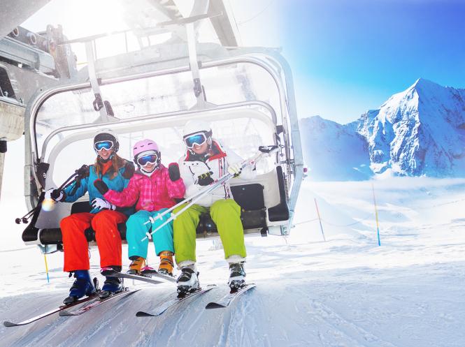 Skiers take a ski lift up the mountain