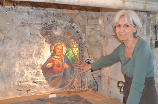 Stained Glass  restorer Jean Chantal next to one of her restoration projects