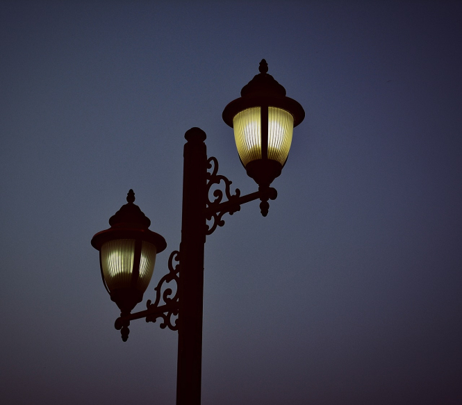 Streetlamps at dusk. Curfew extended in eastern France as new cluster discovered