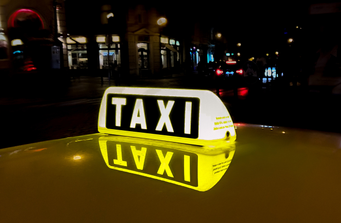 Taxi sign on top of a car. Taxi driver faces lawsuit for €230 fee for Roissy-Paris trip