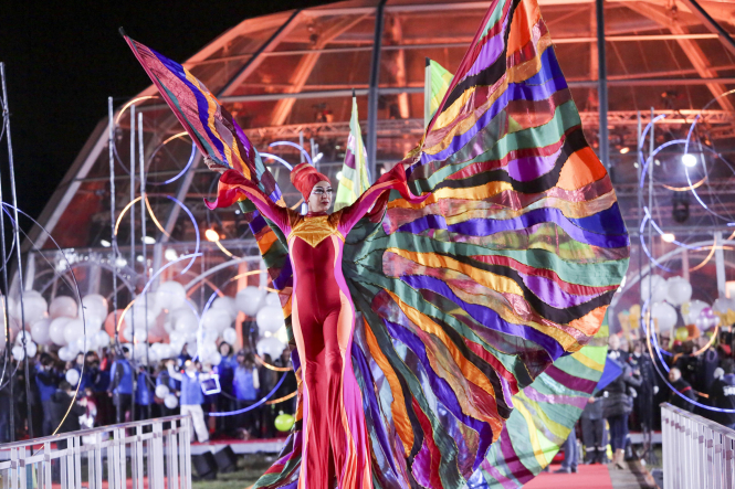 Very colourful image of red-dressed woman with enormous multi-coloured veil as part of TV parade