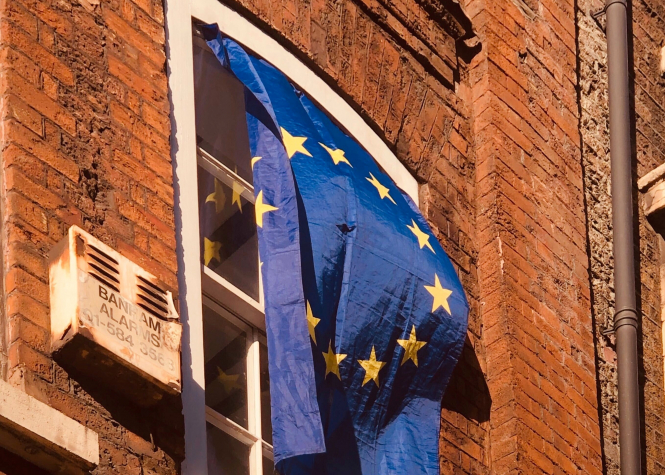 EU flag hangs outside of a window.