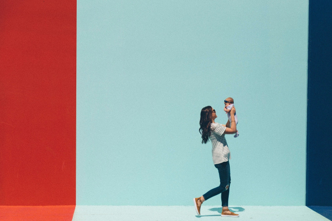 A mother and a child walking past a brightly coloured wall.