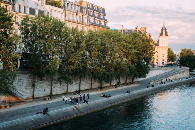 People sitting along the banks of the river Seine in Paris. Swimming in the Seine on track for 2024 as water quality improves