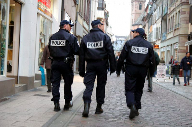 Three police officers waking down a street. Formal call to end racial profiling by police in France