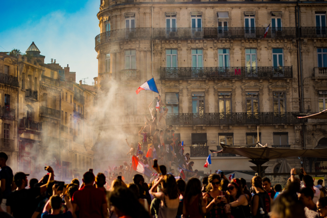 People waving flags of France in a celebration in Comédie, Montpellier, France.
