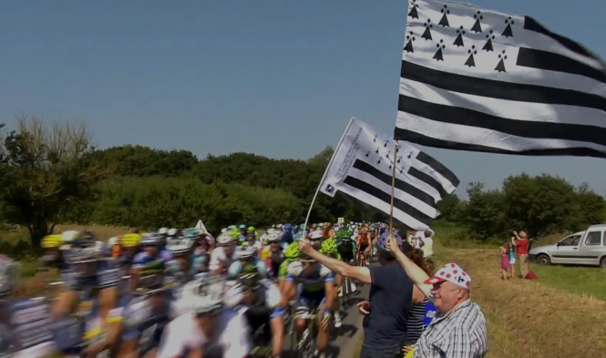 The Tour de France peloton passes as spectators wave Breton flags. The Tour de France 2021 will now depart from Brest due to Covid