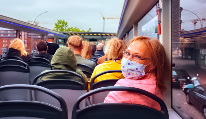 A woman with a mask rides an open-top tourist bus. New restrictions have been introduced in Paris but there are no changes to rules on tourists visiting France