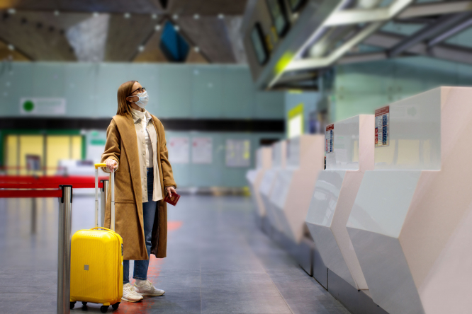 A woman at an airport wearing a mask and holding a suitcase