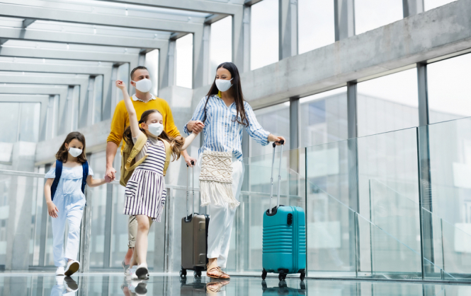 A family at an airport wearing Covid masks