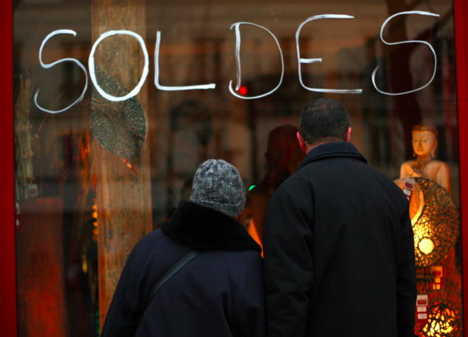Two people looking at objects in a sale through a shop window. What's new in France from January 1, 2021