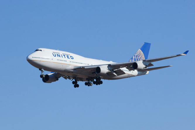 United Airlines plane flying through blue sky. New report on error causing near runway collision of US plane in Paris