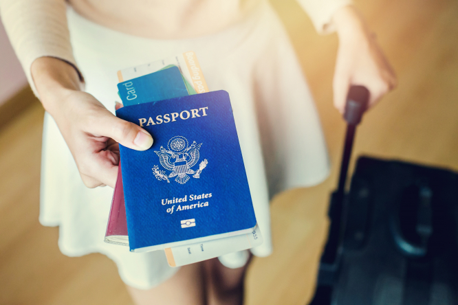 A person with a suitcase holding a US passport