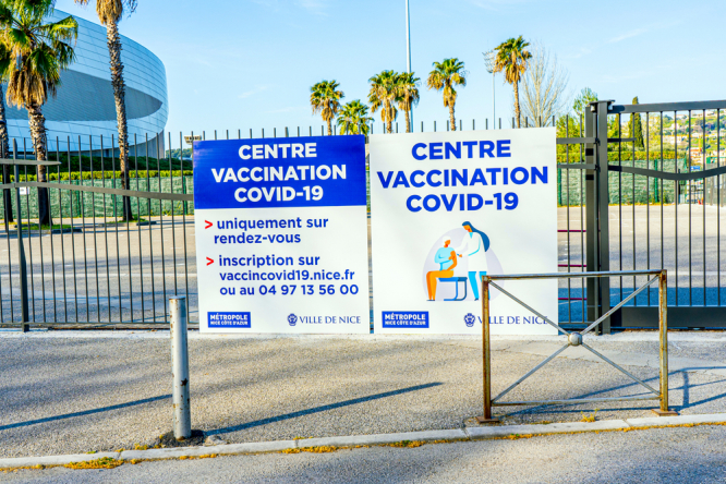 Signs to a vaccination centre in Nice, with palm trees visible behind. France allows holidaymakers to get second Covid jab while away