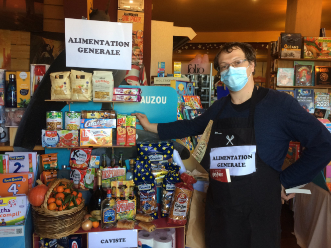 A worker at le Verbe Au Soleil in front of the bookshop's food area. Supermarkets in France may sell 'non-essentials' today