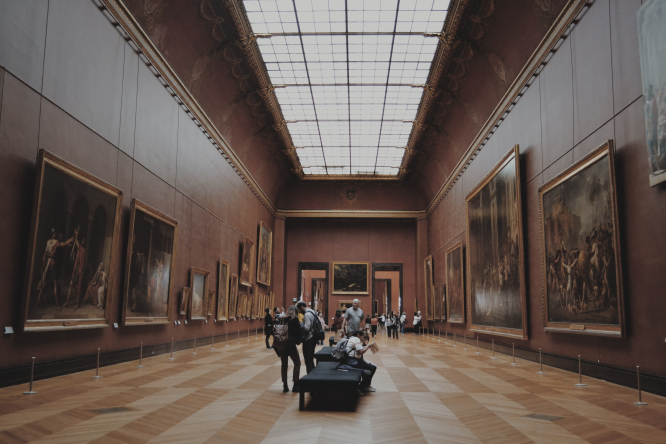 Visitors looking at artworks in the Louvre museum. Mayor to reopen museums in French city despite Covid rules
