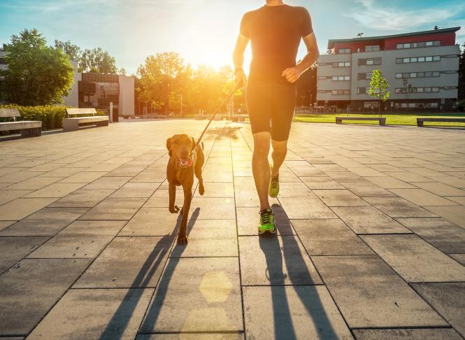 A man runs with a dog