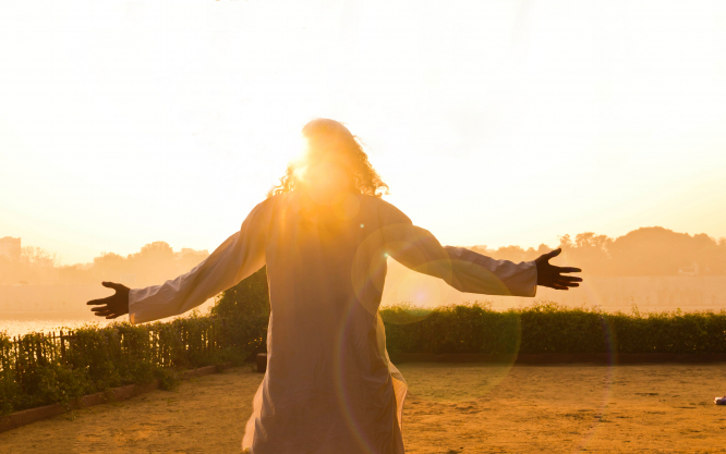 Person standing in floaty top greeting the sun streaming into their face