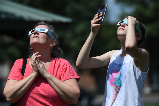 Women look into the sun using solar eclipse glasses. Partial eclipse of the Sun visible in France this week: How to watch