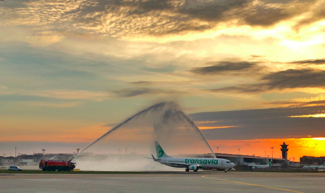 """Two fire engines shoot water forming an archway, as a plane passes underneath. The """"water salute"""" was for the first commercial flight to leave Orly airport since it shutdown during the Covid-19 crisis."""