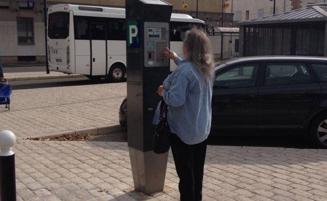 A person paying their parking fee at a car park ticket machine