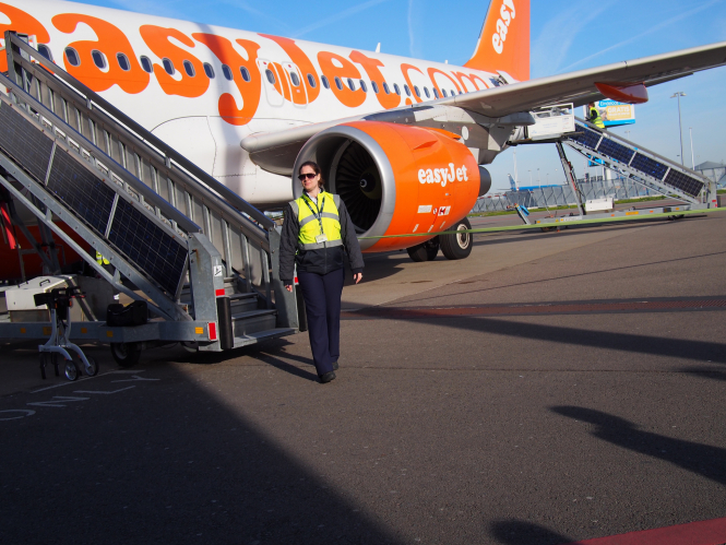 A member of ground crew at the base of moveable steps to an Easyjet aircraft