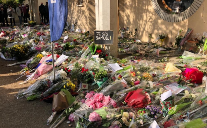 Bouquets of flowers line the floor as a tribute to the murdered French school teacher Samuel Paty